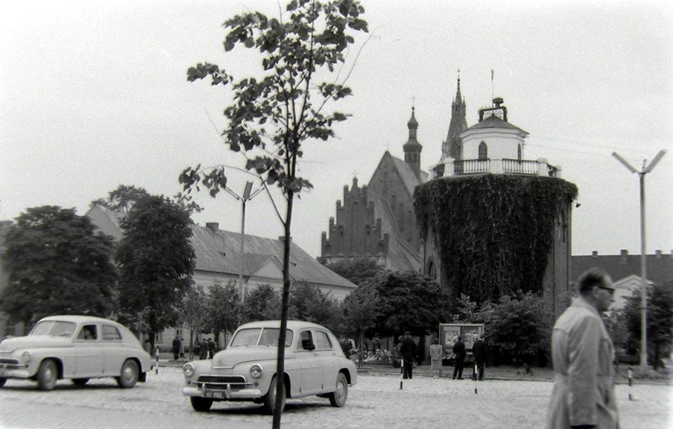 Zdjęcie wieży ciśnień z warszawami na pierwszym planie. Fotografia autorstwa Jana Nosowicza wykonana na początku lat 60-tych XX wieku.