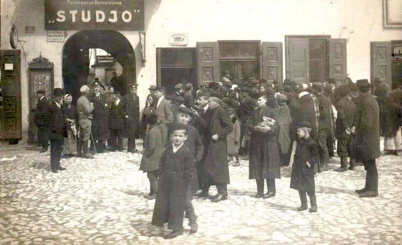 Żydzi przed zakładem fotograficznym w północnej pierzei (późniejszy zakład Dębcowej). Na wprost widoczny napis na szyldziku Owocarnia. Fot. ze zbiorów Piotra Nogiecia.