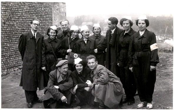 Fotografia z siostrami PCK wykonana prawdopodobnie obok ceglanego wtedy jeszcze budynku PSS, w miejscu późniejszej restauracji Stylowej w latach 50-tych. W głębi po prawej stronie widać przejazd kolejowy na ulicy 29-Listopada. fot=